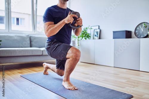 Tablou Canvas Home workout, closeup of athletic man doing lunges with kettlebell at home