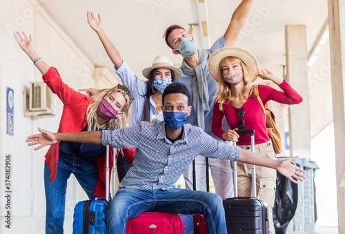Fotografie, Obraz Multiracial group of friends at train station with luggage wearing protective mask