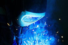 Close-up Of Welder Wearing Mask Working In Factory