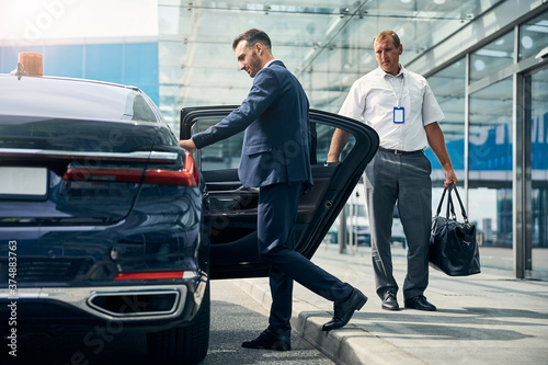 Fototapeta Man in a nice suit opening a car to begin commute from the airport