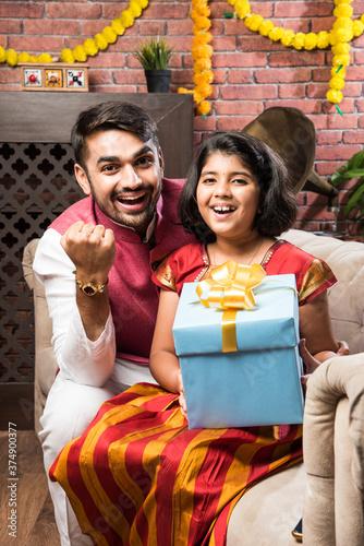 Tablou Canvas Cute little Indian sister tying Rakhi to big brother, celebrating raksha bandhan