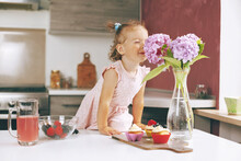Portrait Of A Little Cute Girl Sniffing A Bunch Of Hydrangeas. The Girl Sniffs Flowers, Next To The Table Are Muffins, A Glass Bowl Of Berries And A Glass Of Juice, Side View