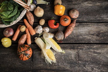 Various Autumn Vegetables Scattered Out Of A Wicker Basket Onto Wooden Boards