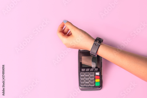 Fotografia Payment for purchases using smart watches and POS terminal on light pink background
