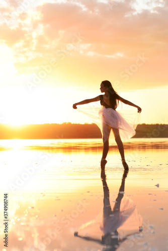 Silhouette of a slender girl ballerina dancing in a transparent airy dress against the backdrop of the setting sun Canvas Print