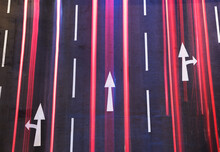 Night Traffic On Road. White Arrow Sign Painted On Black Asphalt