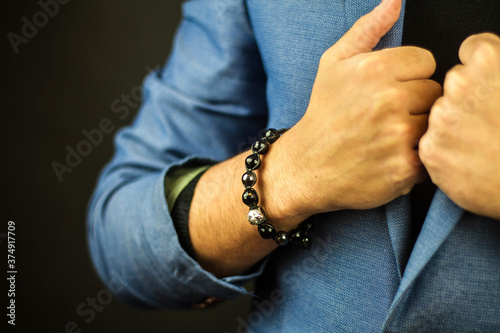 Photo Closeup shot of a man in a suit wearing a beautiful bracelet made of stones
