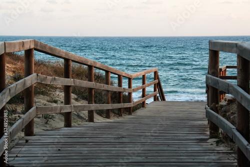 Passerella in legno sulla duna per accesso alla spiaggia Fototapet