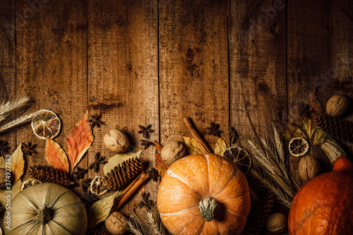 Fototapeta Autumn pumpkins, spikelets and dried flowers on a rough wooden background, top view, free space for text obraz na płótnie