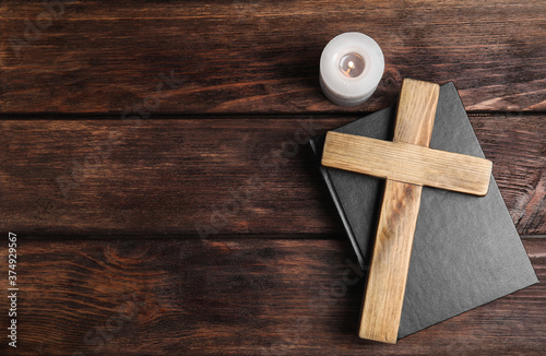 Fotografía Cross, Bible and burning candle on wooden background, flat lay with space for text