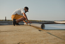 Worker Applies Pvc Membrane Roller On Roof