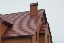 Part Of The House With Red Tiles On The Roof With  A Brick Pipe Against The  Gray Sky
