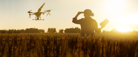 Farmer controls drone sprayer with a digital tablet