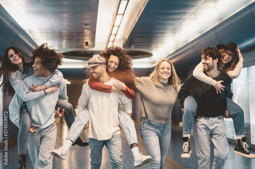 Fototapeta Group young friends having fun piggybacking in underground metropolitan subway -