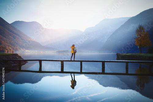 Obraz na plátně girl stands on a wooden bridge
