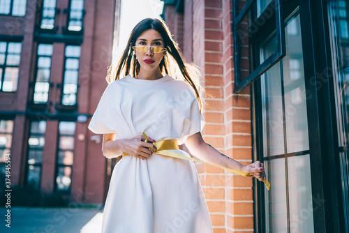 Fototapeta Half length portrait of beautiful teenage female model looking at camera during