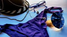 Endecha Plana De Objetos Veraniegos Con Bikini De Color Morado, Sombrero Negro Con Collar, Gafas Y Auriculares Blancos Y Unas Conchas Con Sombrilla Al Sol. Composición Veraniega.
