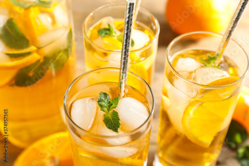 Fotografia Delicious refreshing drink with orange slices on table, closeup