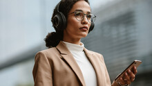 Businesswoman Commuting And Listening To Music