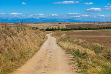 Rural Landscape Of A Dirt Road That Connects One Town With Another Town With Blue Sky And White Clouds