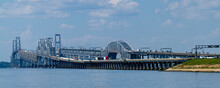A Day Time Wide Angle Image Showing The Rush Hour Traffic On Chesapeake Bay Bridge. It Features Detailed View Of The Bridge With Columns And Suspensions As Well As The Boats Passing Under.