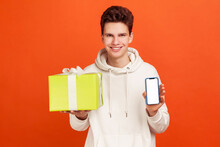 Cheerful Young Man In Casual Style Hoodie Holding Gift Box And White Screen Smartphone, Application For Presents Order And Delivery. Indoor Studio Shot Isolated On Orange Background