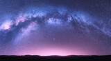 Fototapeta Na sufit - Milky Way arch. Fantastic night landscape with bright arched milky way, purple sky with stars, pink light and hills. Beautiful scene with universe. Space background with starry sky. Galaxy and nature