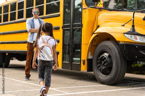 school bus driver is standing in front of his bus Wallpaper Mural