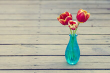 Three Colorful Tulips In Blue Vase On Wood Surface