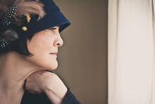Woman Wearing Vintage Blue Hat With Feathers Staring Out Window