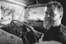 Bearded Tattooed Man Sitting Inside Vintage Truck