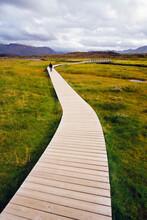 Boardwalk Meandering Towards Rugged Cliffs And Stormy Sky At Thingvellir National Park Near Reykjavik, Iceland, Polar Regions