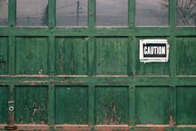 Green Garage Door With Caution Sign