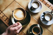 A Hand Lifts A Cup Of Cappucci...