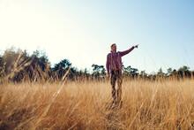 Man Standing In High Grass Poi...