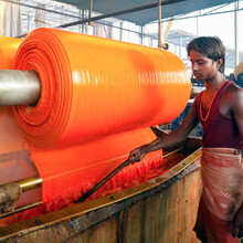 Portrait Of A Factory Worker, Newly Dyed Fabric Being Washed And Rolled, Sari Garment Factory, Jaipur, Rajasthan, India