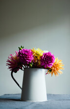 Brightly Coloured Dahlias In An Enamelware Vase On A Tablecloth