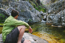 Hiker Resting By A Rock Pool Whilst Watching A Small Waterfall
