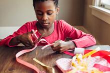 Black Girl's Hand Cutting Pink Ribbon