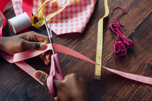 Black Girl Cutting Pink Ribbon For A Craft