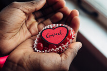"""Black Girl's Palms Holding Red Candy And A Paper Heard Spelling """"""""loved"""""""""""