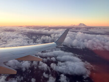 Horizontal View Of Mount Rainier And Clouds At Sunrise From The Airplane
