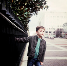 Young Boy Portrait On Wrought Iron Fence In Downtown Washington DC