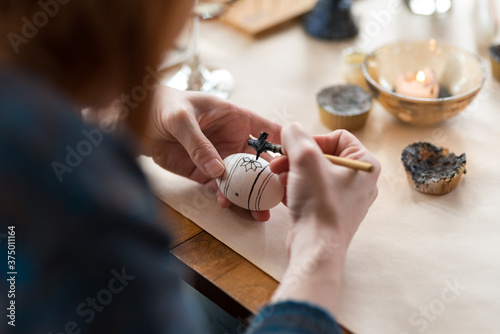 Canvas Print Woman carefully paints design on egg for Easter holiday