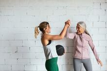 Happy Women In Sportswear Celebrating Success In Gym
