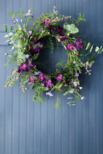 Wreath Of Wild Flowers On Old Wooden Wall