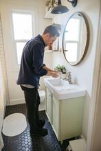 Man Washing Hands In Bathroom ...