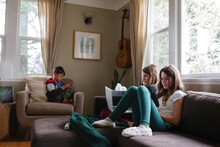 Kids Using Screens On Couch At Home. Technology Tablets And Computers At Home.