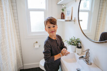 Young Boy Washing Hands In Bathroom At Home.