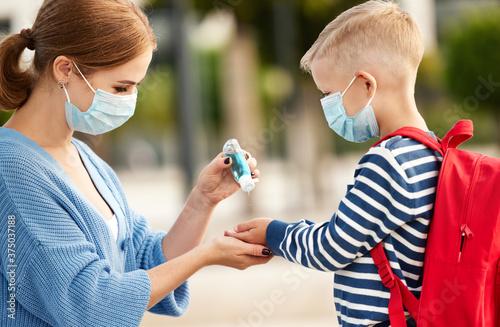 Obraz Mother disinfecting hands of schoolboy. - fototapety do salonu